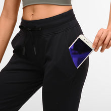 Load image into Gallery viewer, These Solid Slim Fit Drawstring Joggers - Black are great for either in studio, at the gym, work at home or on the go. Featuring mid-rise, slim fit and adjustable drawstring, these cuffed joggers are as versatile as they are comfortable. Open deep pockets can store essentials like a phone, keys, cards etc. Buttery soft material is breathable, moisture-wicking and dries quickly. Perfect for yoga, cardio, jogging as well as errand running and lounging. Complete the look with a crop top or crop tank.