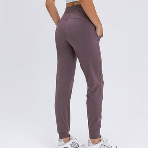 These Solid Slim Fit Drawstring Joggers - Mystic Purple are great for either in studio, at the gym, work at home or on the go. Featuring mid-rise, slim fit and adjustable drawstring, these cuffed joggers are as versatile as they are comfortable. Open deep pockets can store essentials like a phone, keys, cards etc. Buttery soft material is breathable, moisture-wicking and dries quickly. Perfect for yoga, cardio, jogging as well as errand running and lounging. Complete the look with a crop top or crop tank.