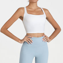 Load image into Gallery viewer, Bring style to the yoga studio in this Strappy Crisscross Padded Crop Tank Sports Bra - White. Featuring square neck and full-on wide crisscross straps on the back, this Strappy Crisscross Padded Crop Tank Sports Bra is ideal for low to medium impact activities such as yoga and weight training. With 14-16 inch / 37-41 cm shortened length, this flattering padded crop tank top kisses your high waisted leggings, and is easy to layer. Complete the look with our Solid Hidden Pocket 7/8 Leggings.