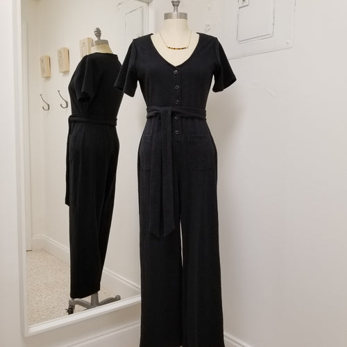 short sleeve black wide leg knit jumpsuit with v neck button front and tie at the waistband