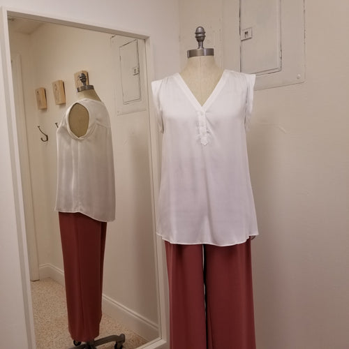 white sleeveless modal top with v neck style and 3 small buttons