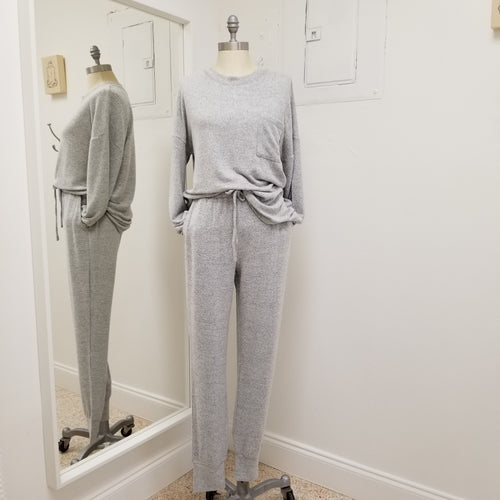 soft grey jogger set top has round collar and front pocket bottoms have drawstring elastic waistband and pockets