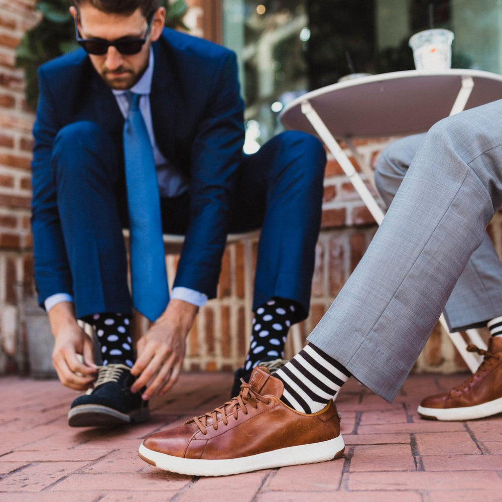 Two men wearing our black and white dress socks and fun fashion polka dot socks.