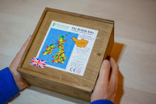 Load image into Gallery viewer, Two hand holding a stained wooden box, with a sliding lid. On the box is a label showing the Counties of the British Isles puzzle inside