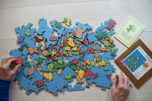 A pile of all the pieces of the Counties of the British Isles puzzle. There are two hands holding two pieces of the puzzle either side of the pile.