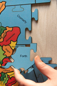 A partially made puzzle of the counties of the British isles. A hand is holding the sea area piece labelled Forth.