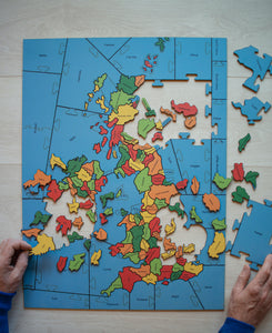 A partially made wooden jigsaw puzzle of the counties of the British Isles with two hands holding two pieces.