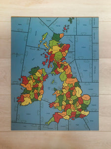 a completed wooden Puzzle showing the Counties of the British isles on a pale wood background.