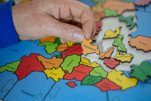 a partially made jigsaw puzzle of the counties of the British Isles, a hand is holding the piece of Oxfordshire.
