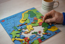 Load image into Gallery viewer, A wooden puzzle of the Countries of Europe. A hand on the right of the puzzle a hand holds the Romania Piece. There is a cup of tea in the background.
