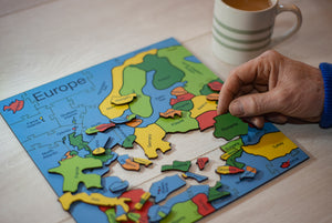 A wooden puzzle of the Countries of Europe. A hand on the right of the puzzle a hand holds the Romania Piece. There is a cup of tea in the background.