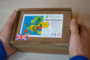 Two hands hold a brown wooden box. on the box lid is the label showing the details of the Countries of Europe Jigsaw Puzzle