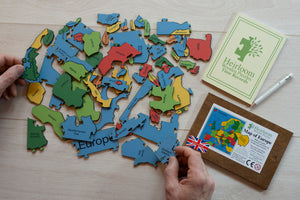 A pile of the pieces in the Countries of Europe Jigsaw Puzzle. Two hands hold pieces of the puzzle either side of the puzzle.