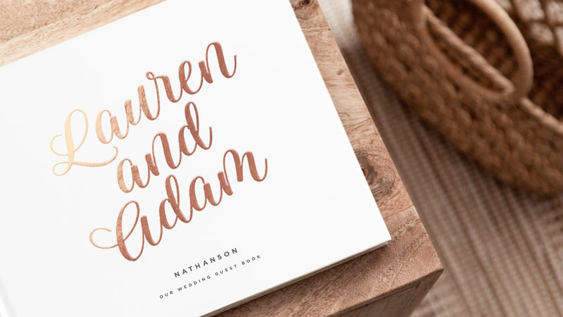 "white hard cover guest book sitting on wood table with gold lettering that reads ""Lauren and Adam"""
