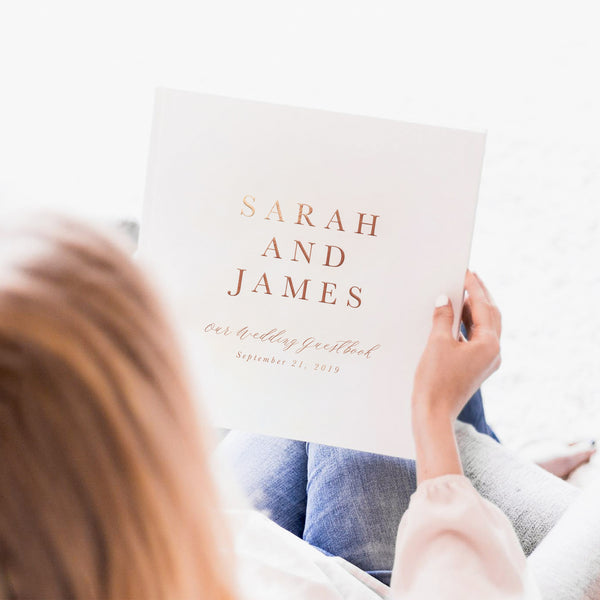 "woman with red hair holding a hard cover guest book that reads ""Sarah and James, our wedding guest book"""