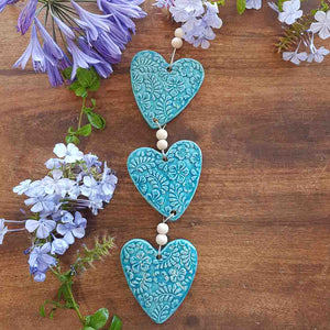 3 Turquoise Coloured Embossed Hearts on a String with Beads. (approx. 38 x 8cm to top of string)