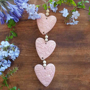3 Pink Embossed Hearts on a String with Beads. (approx. 38 x 8cm to top of string)