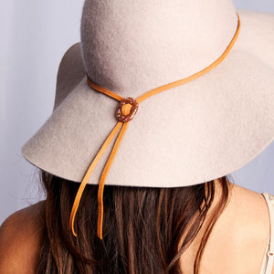 Person wearing glass bolo tie necklace on brown leather with silver tips