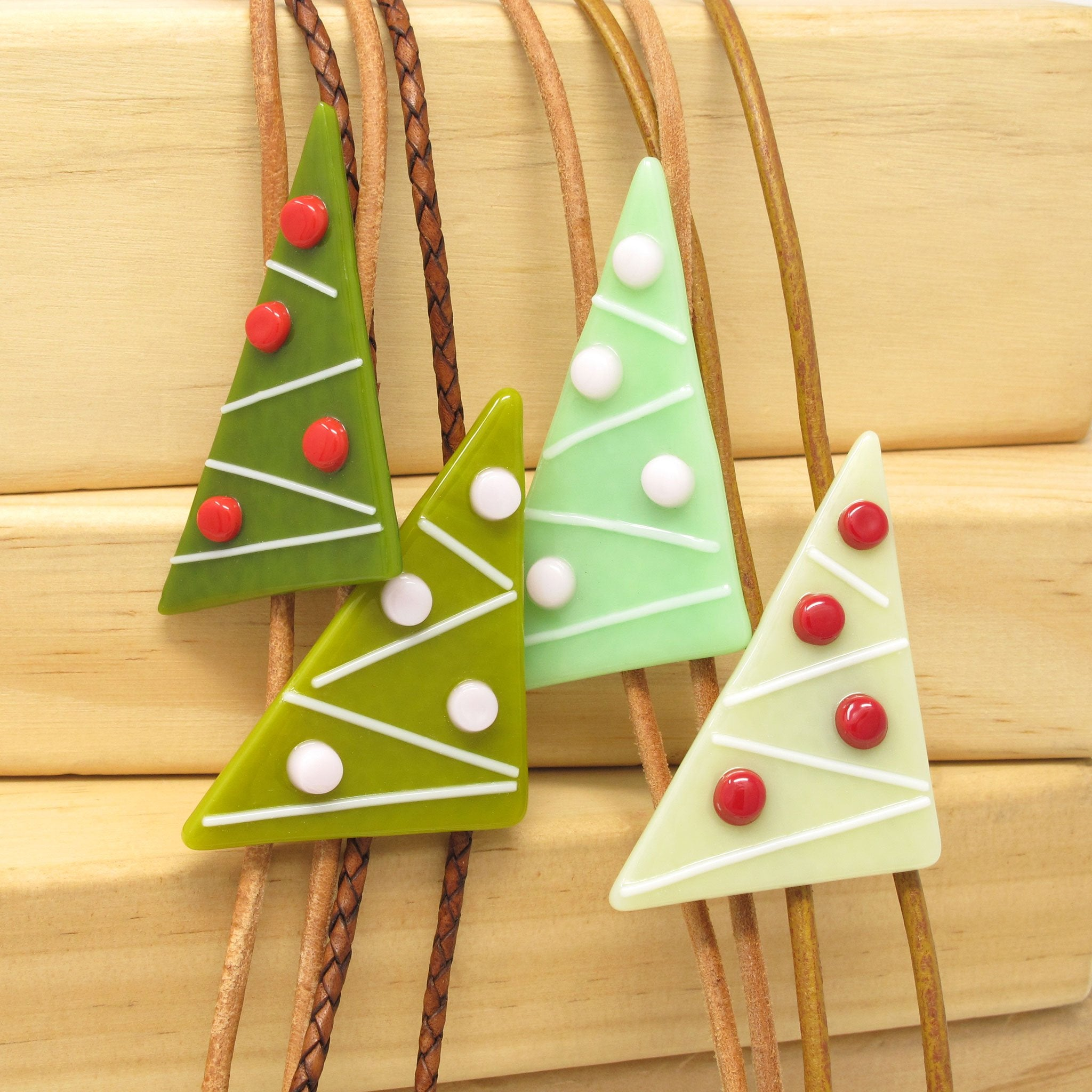 Selection of Kismet's modern Christmas tree bolos on brown leather cord with silver plate tips