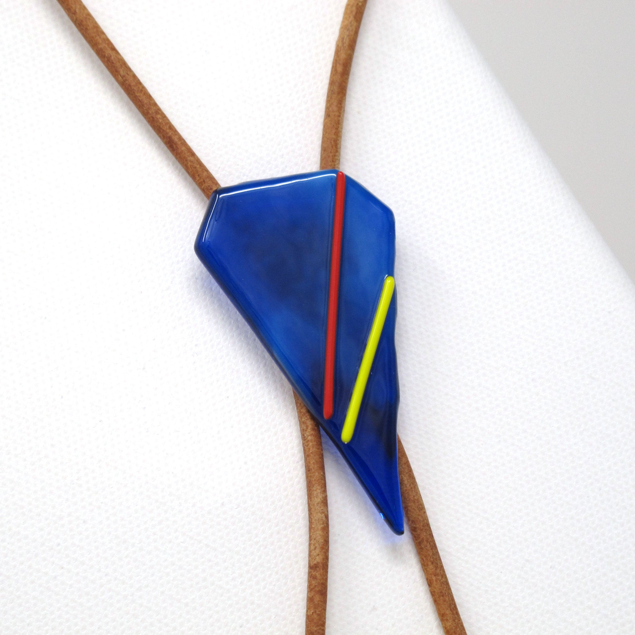 Modern glass bolo tie necklace on brown leather with silver tips, cobalt blue