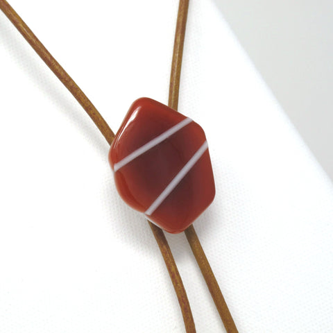 Close up of modern glass bolo tie necklace on brown leather with silver tips, ruby red with white bars