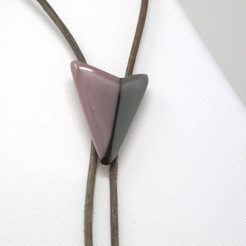 Close up of modern glass bolo tie necklace on gray leather with silver tips, mauve lavender gray
