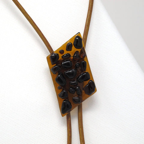 Close up of modern glass bolo tie necklace on brown leather with silver tips, tortoise shell