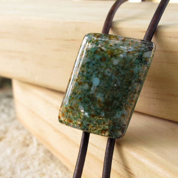 Close up of Symphony Edition modern glass bolo tie necklace on brown leather with silver tips, turquoise stone