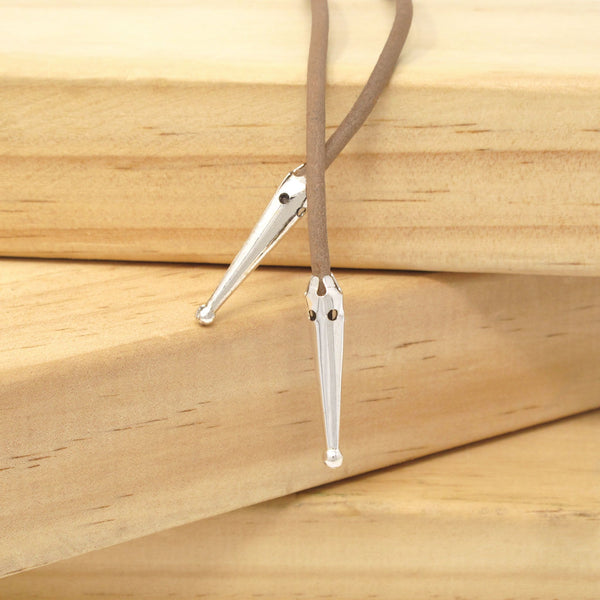 Close-up of silver plate bolo tie tips