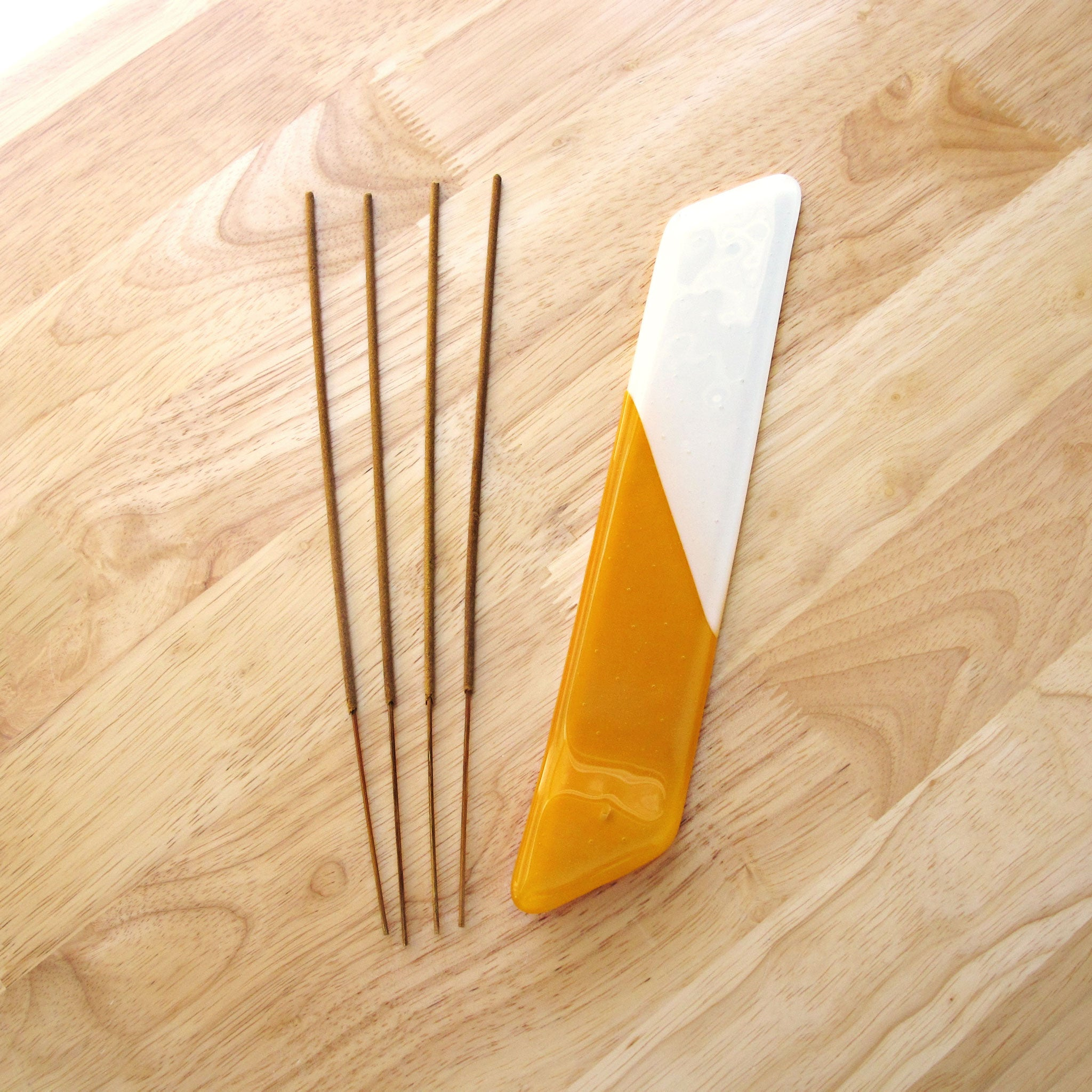 Katie Kismet yellow and white incense burner with four sticks of incense (flat view)