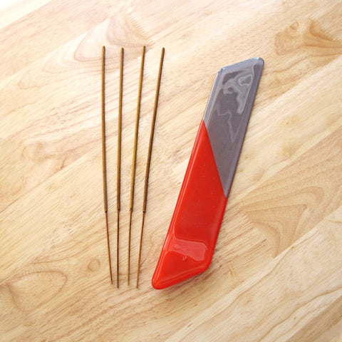 Katie Kismet red and gray incense burner with four sticks of incense (flat view)