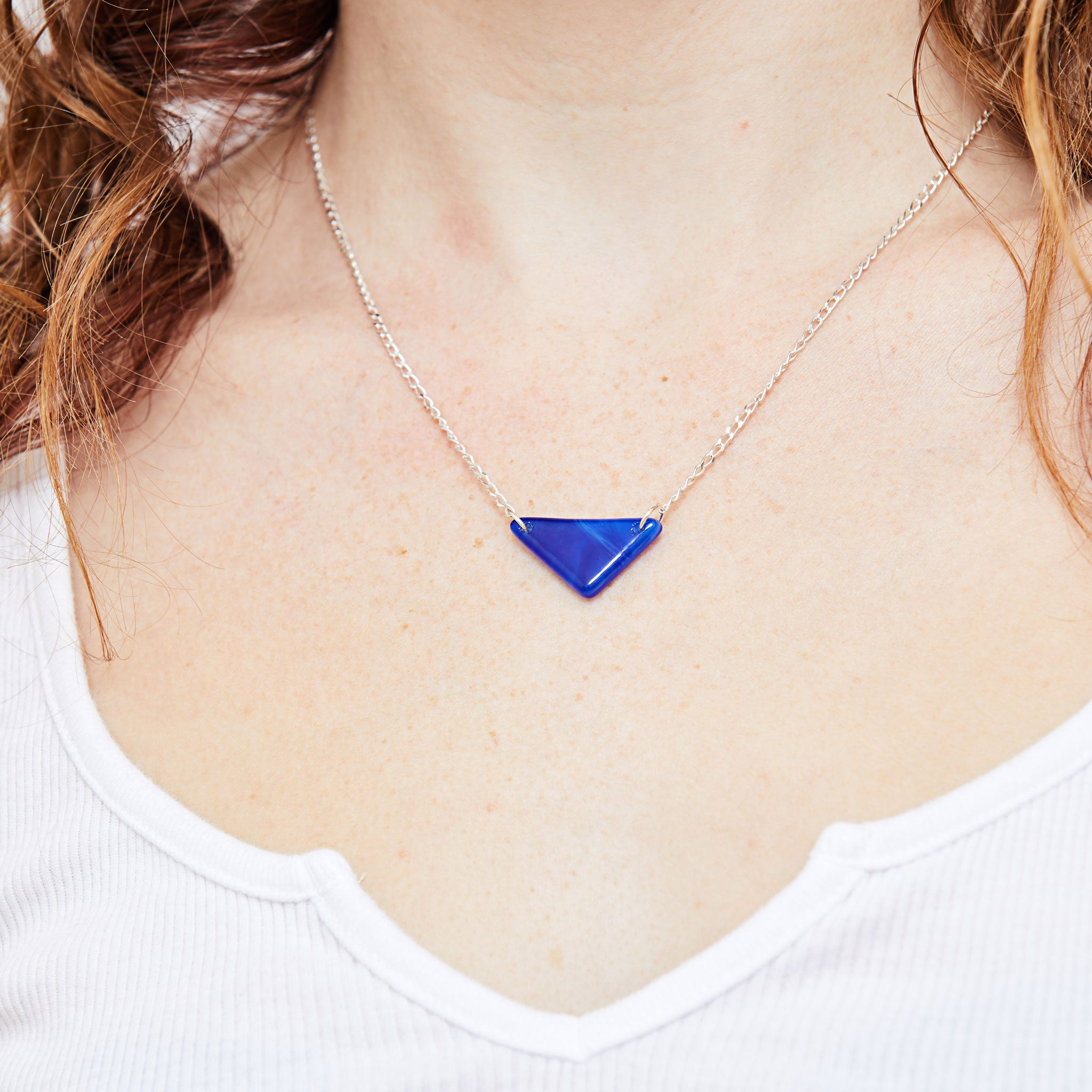 Model wearing sterling silver necklace with handmade blue glass accent piece