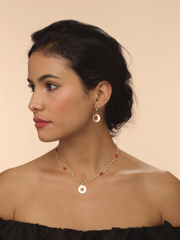 Model wearing pirate gold earring with moon talisman.