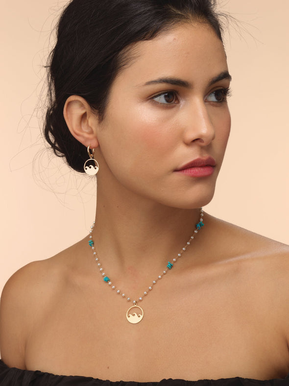 model wearing hand strung pearl necklace with gold wave talisman and blue coral.