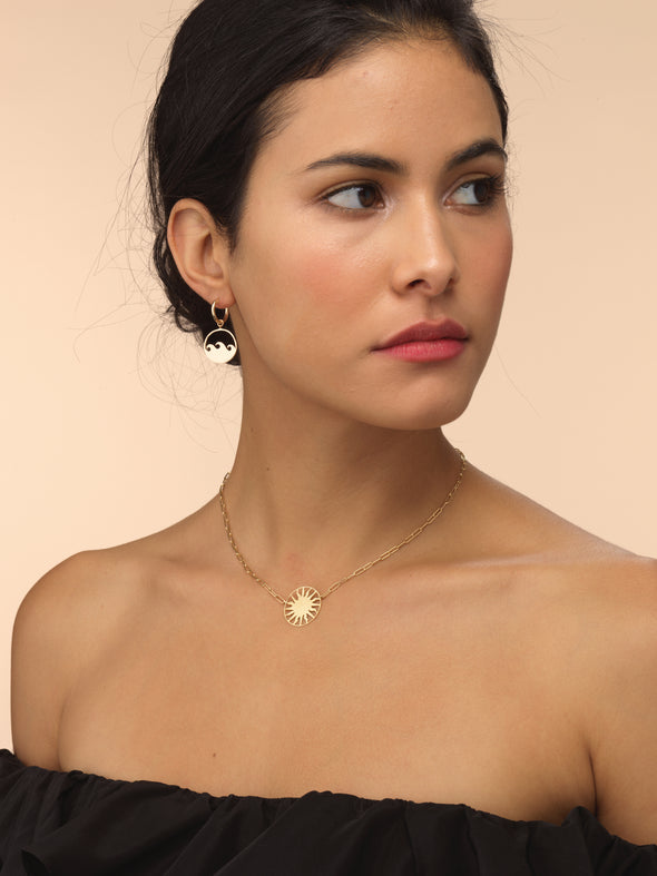 Model wearing gold roman sun necklace with think chain.
