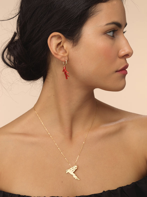 Model wearing gold bird pendant inspired by Gazza Ladra