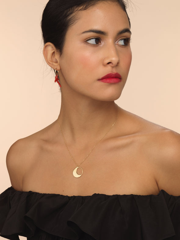 Model wearing gold moon necklace with thin chain.