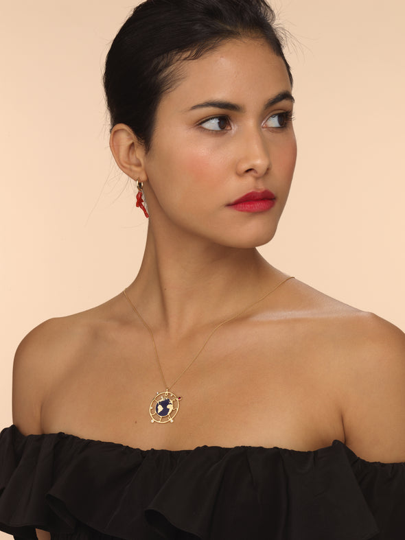 Model wearing gold earth necklace with blue enamel, diamonds and ruby detailing.