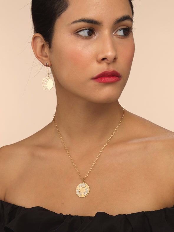 Model wearing gold necklace with diamond recycle symbol.