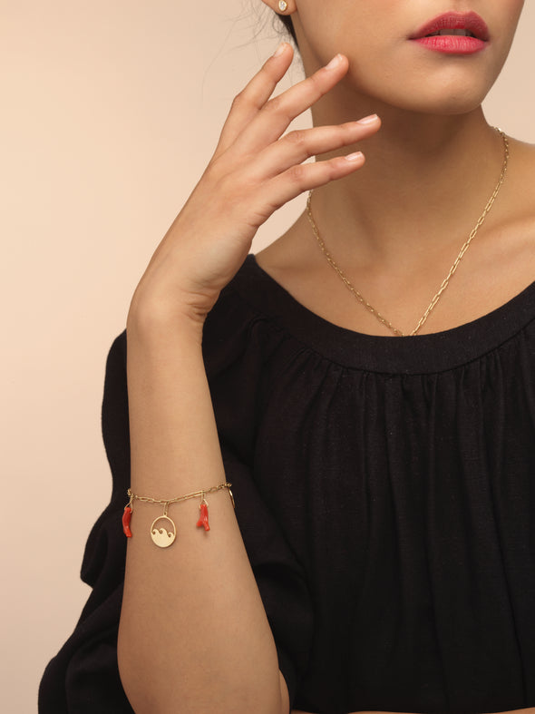 Model wearing gold charm bracelet with red coral charms.