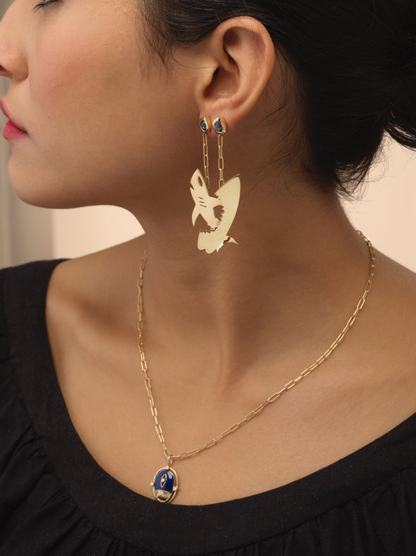 Model wearing gold shark and surfboard earrings.