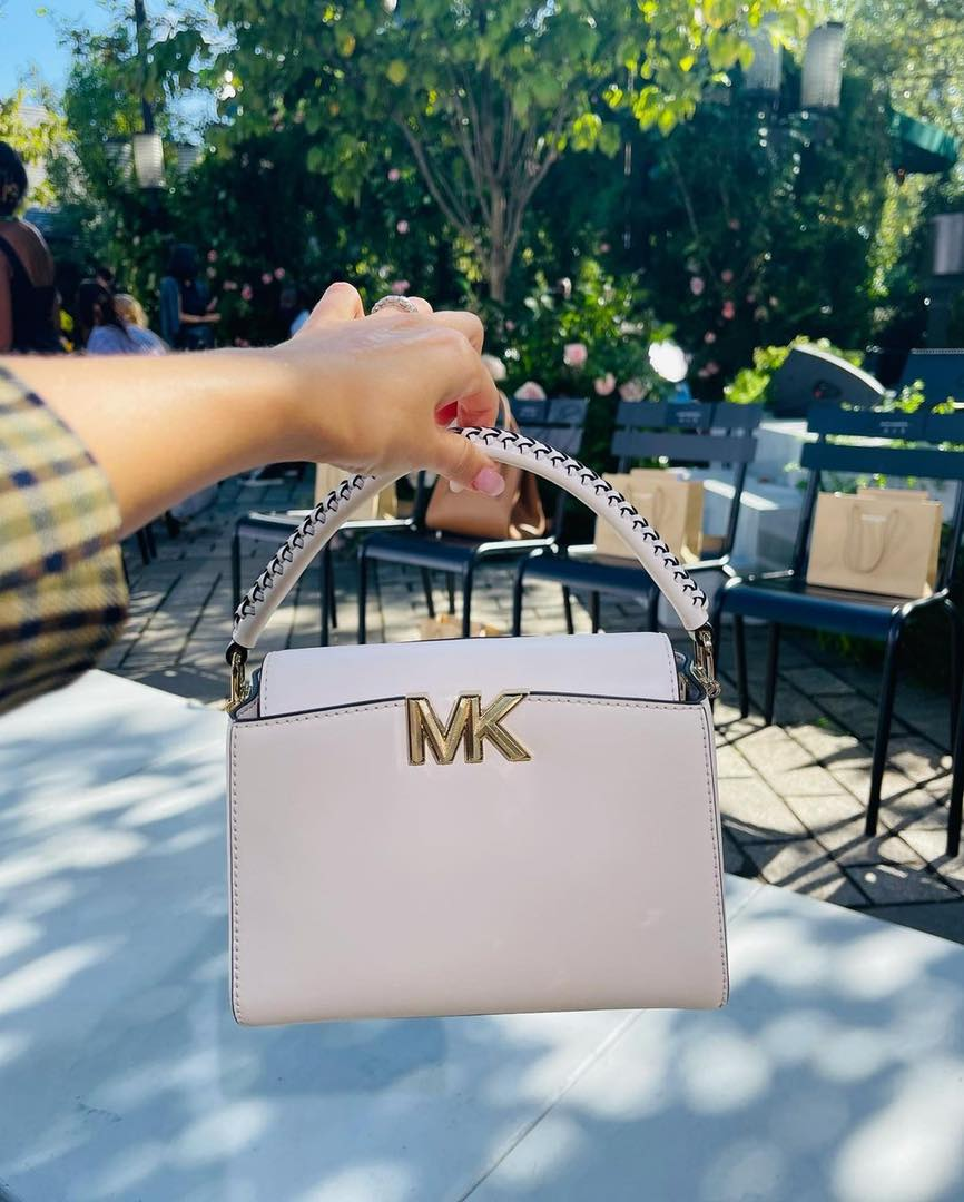 Hand holding out pink Michael Kors purse