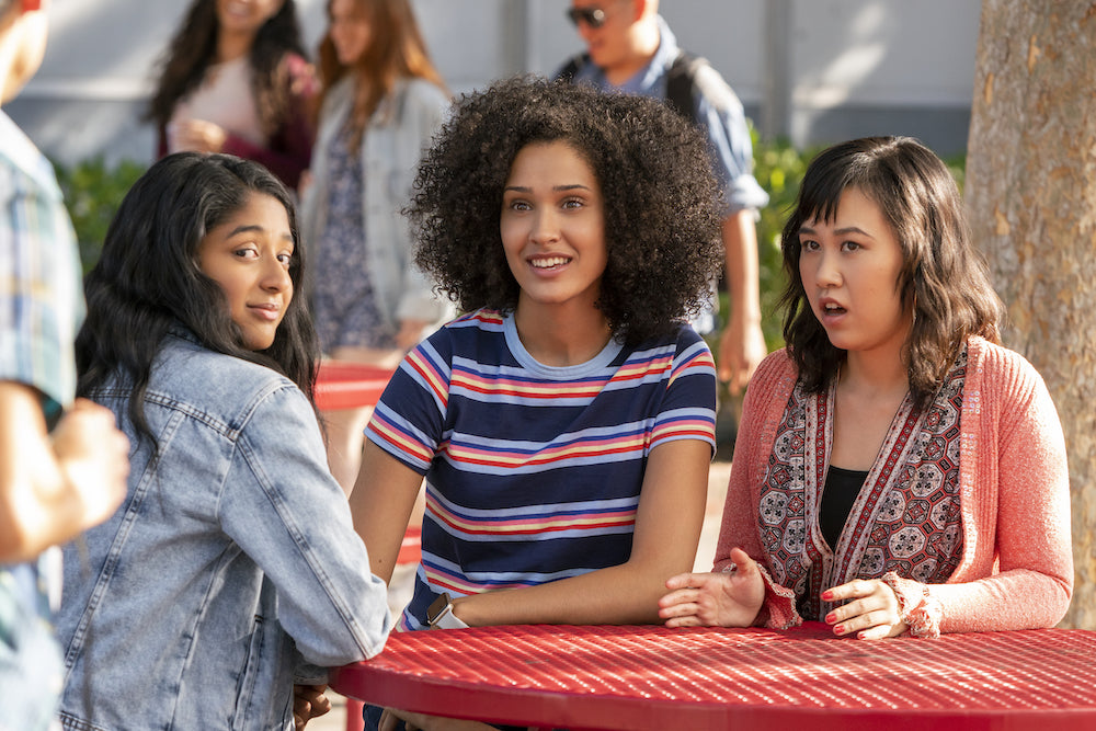 Three women characters of Never Have I Ever sitting at picnic table