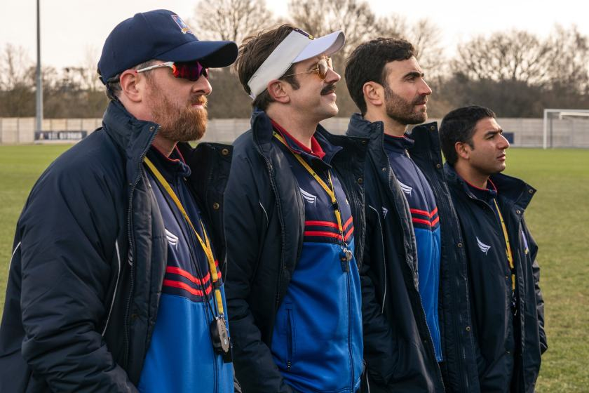 """four characters of """"Ted Lasso"""" standing in line on soccer field"""