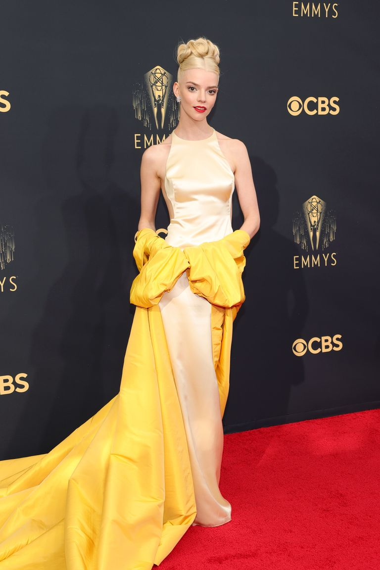 Anya Taylor-Joy wearing yellow and cream dress and halter standing on Emmys red carpet 2021