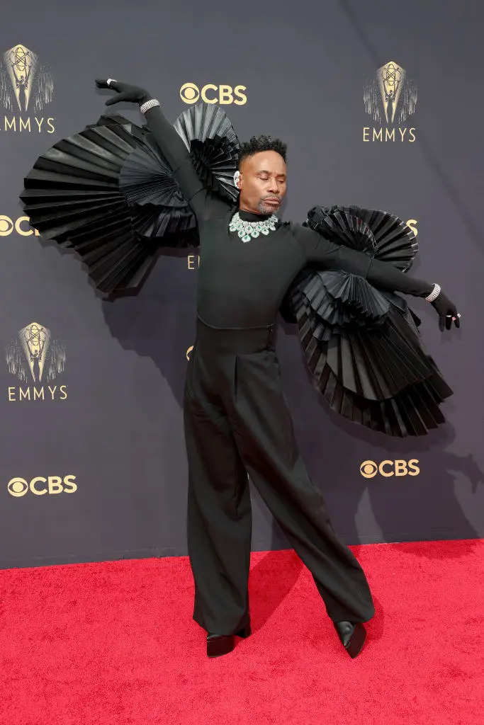 Billy Porter wearing black winged suit, arms outstretched, standing on Emmys Red Carpet