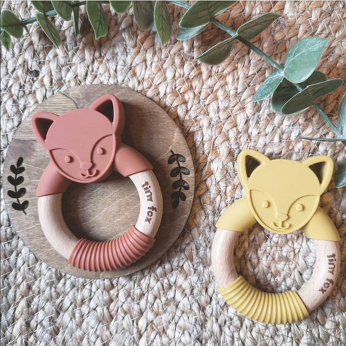 Silicone and beechwood fox face teething ring in mustard and cinnamon on a natural background.