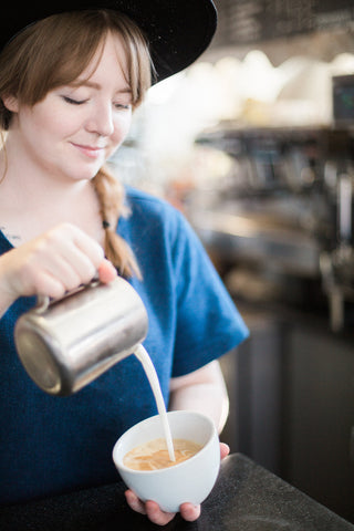 Barista Pouring Steamed Soy Milk into Coffee at Hugo Coffee