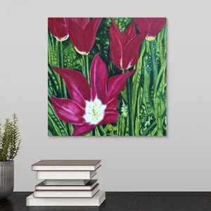 A painting of dark magenta tulips in full bloom, surrounded by a lush, vivid green garden backdrop hanging over desk