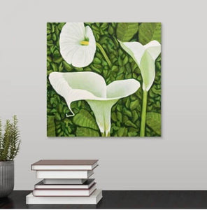A painting, by fine artist Nancy McLennon, of a trio of calla lilies in a green garden background, hanging over a desk